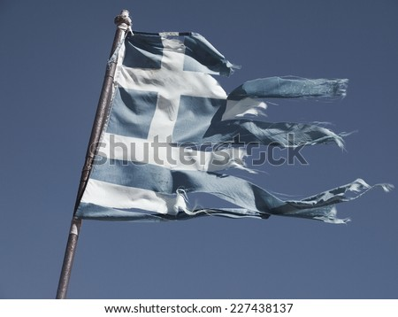 Greek torn flag fluttering in the wind, posted signs on a rusty pole - stock photo