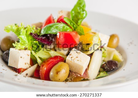 Greek Vegetable salad with feta cheese, olives, cucumbers, tomatoes, pepper  on the white plate isolated om white background - stock photo