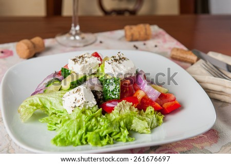 Greek Vegetable salad with feta cheese, olives, cucumbers, tomatoes,pepper  on the white plate on setting restaraunt table - stock photo