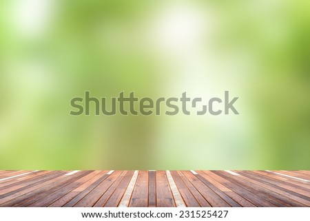 Green abstract blur nature background  with wooden floor - stock photo