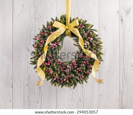 Green advents wreath with autumn decoration in front of a white wooden background - stock photo