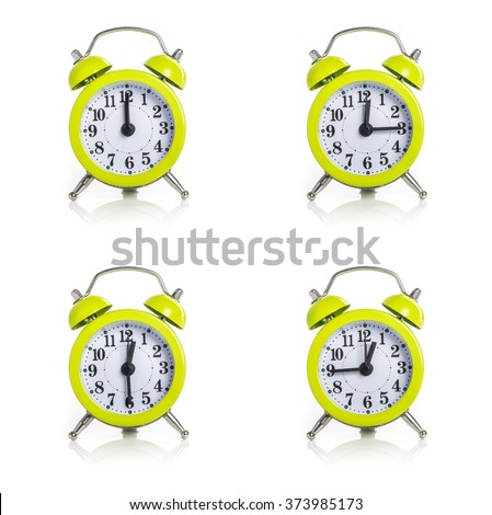 Green alarm clock showing differnt times on white back ground - stock photo