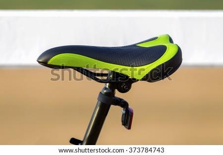 green and black bike saddle in blurry background  - stock photo