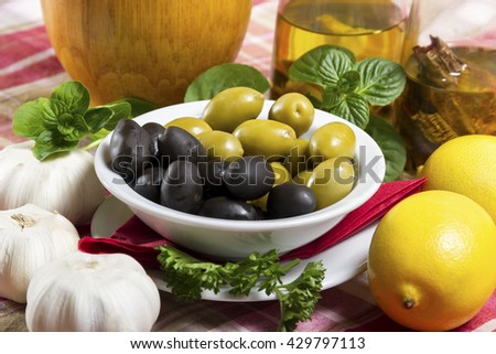 Green and black olives in a white bowl with a saucer, spicy olive oil in glass bottles, lemon, basil and garlic placed on the table. - stock photo