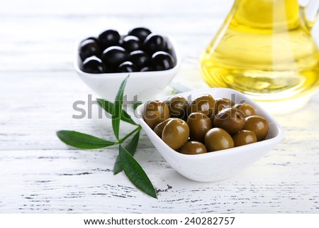 Green and black olives in bowl on white wooden background - stock photo
