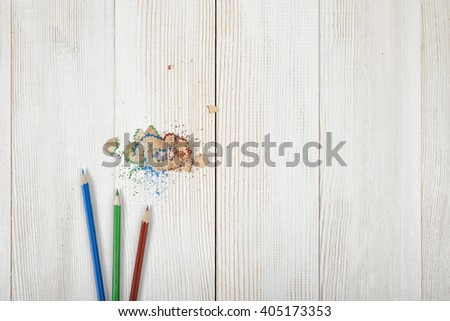 Green and blue colored pencils with its shavings on wooden plank - stock photo