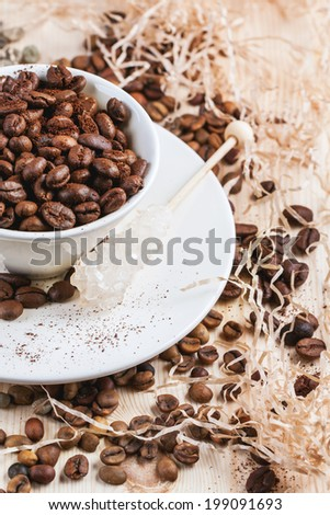 Green and brown decaf unroasted coffee beans and cup of roasted coffee beans on wooden table with chips. - stock photo