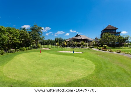 Green and holes in front of Golf clubhouse in Bali, Indonesia - stock photo