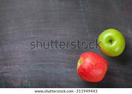 Green and red apples on blackboard or chalkboard background. Top view with copy space - stock photo