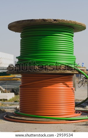 Green and red electricity cable on wooden spools on construction area. Focus on the spools. - stock photo