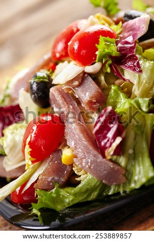 Green and red salad with tuna, cherry and olives, healthy diet food - stock photo