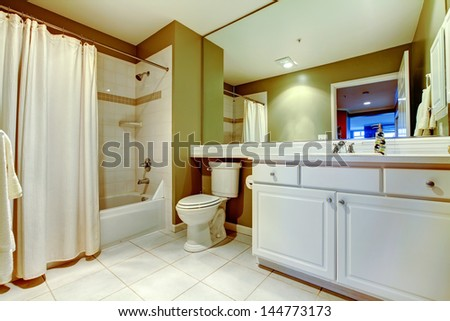 Green and white bathroom with sink and tub with curtain. - stock photo