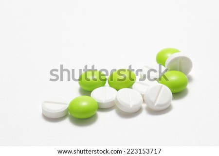 Green and white pills on white background  - stock photo