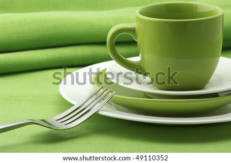 Green and white plates and cup, stainless fork and knife on green linen tablecloth with napkins. - stock photo