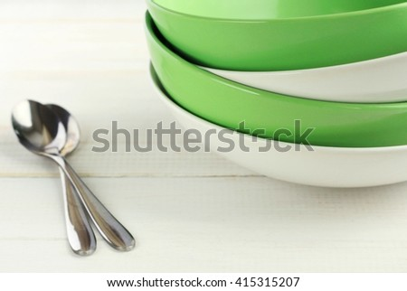 Green and white plates in pile on wooden white table.  - stock photo