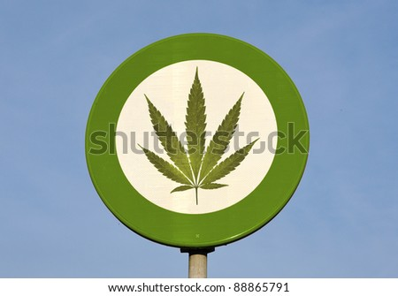 Green and white round reflective sign with Cannabis leaf - stock photo