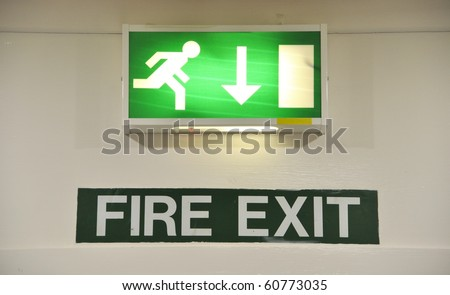 green and white warning sign glowing regarding fire exit emergency - stock photo