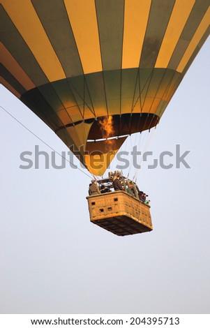 Green and yellow balloon flying over the Serengeti National Park, Tanzania - stock photo