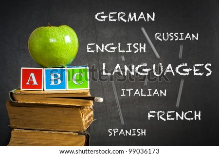 Green apple and ABC on old books against blackboard with with the drawn scheme of studying of languages. School concept - stock photo