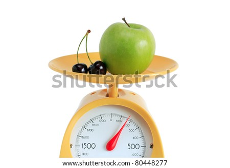 Green apple and cherry lying on yellow kitchen scale. Isolated on white background with clipping path - stock photo