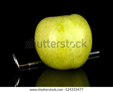 Green apple and dental tool isolated on black - stock photo