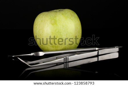 Green apple and dental tools isolated on black - stock photo
