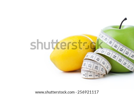 green apple and lemon with measuring tape isolated on white background, close up  - stock photo
