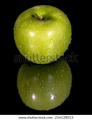 Green apple and reflection with water drops - stock photo