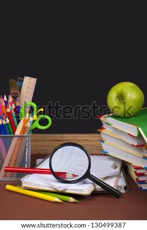 green apple,  board, books, pencils, opened empty notebook lie on school desk - stock photo