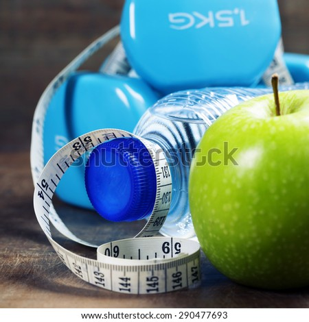 Green apple, dumbbells, water and measuring tape. Health, sport and diet concept - stock photo