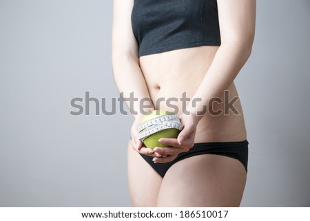 Green apple in female hands on gray background. Body care. Weight loss, diet - stock photo
