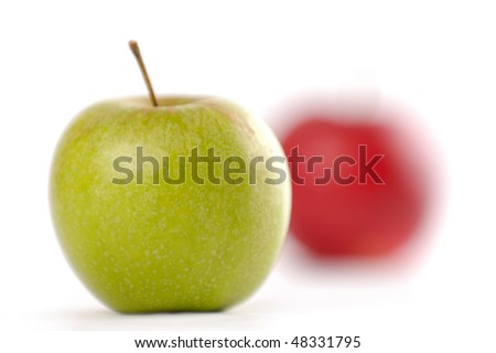 Green apple in focus and red apple out of focus isolated on white background - stock photo