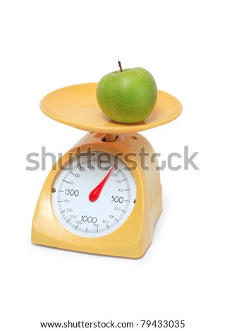 Green apple lying on yellow kitchen scale. Isolated on white background with clipping path - stock photo