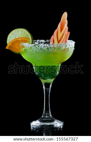 green apple margarita isolated on a black background with an apple garnish - stock photo