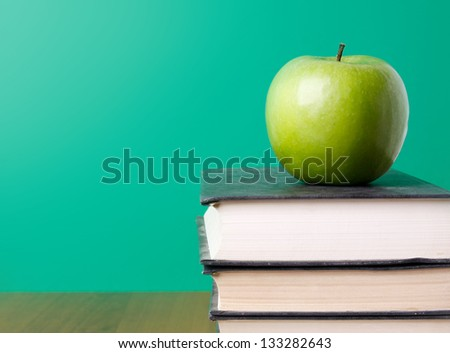 Green apple on a pile of book, isolated on green background - stock photo