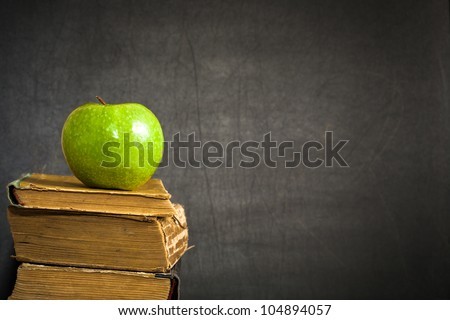 "Green apple on old book against blackboard with space for text ""Back to school!"". School concept - stock photo"