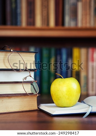 green apple on the open book with books and glasses - stock photo