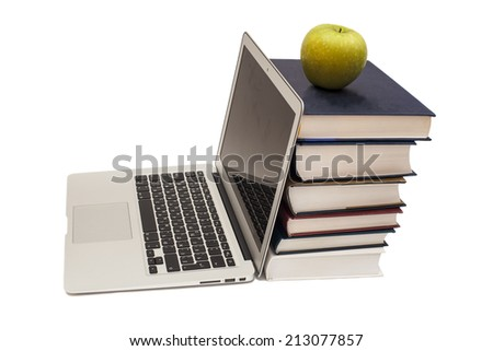 Green apple sitting on top of computer and books  - stock photo