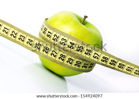 green apple with a measure tape diagonal - stock photo