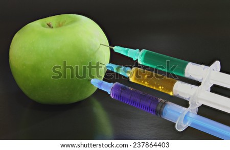 Green apple with syringes on the black background - stock photo