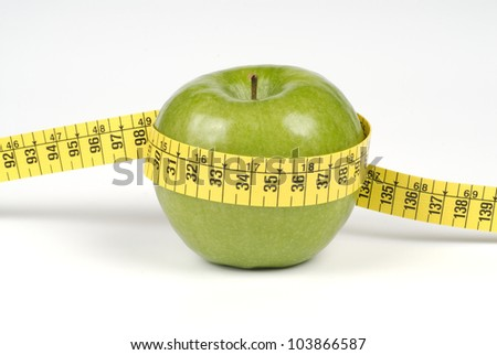 Green apple with tape measure - stock photo
