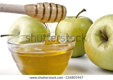 Green apples and a bowl of honey over white. Illustration of Rosh Hashanah (jewish new year) or Savior of the Apple Feast Day - stock photo