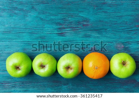 Green apples and one orange over rustic wooden background - stock photo