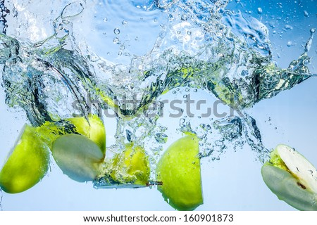 Green apples. Fruits fall deeply under water with a big splash - stock photo