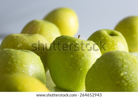 Green apples in drops of water - stock photo