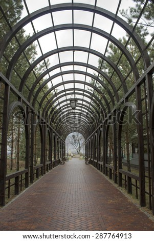 Green arch and a walk in the park - stock photo