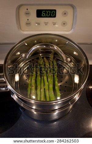 Green asparagus cooking on a stove in a stainless steel steamer pot. - stock photo