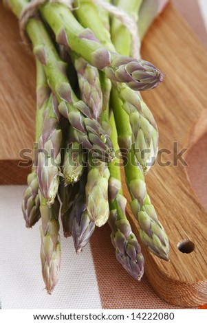 Green asparagus on a wooden board, shallow DOF - stock photo