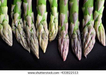 green asparagus on rustic black background - stock photo