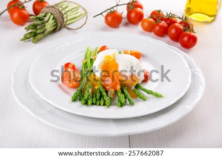 Green asparagus stems with soft-boiled egg, tomato and sauce. - stock photo